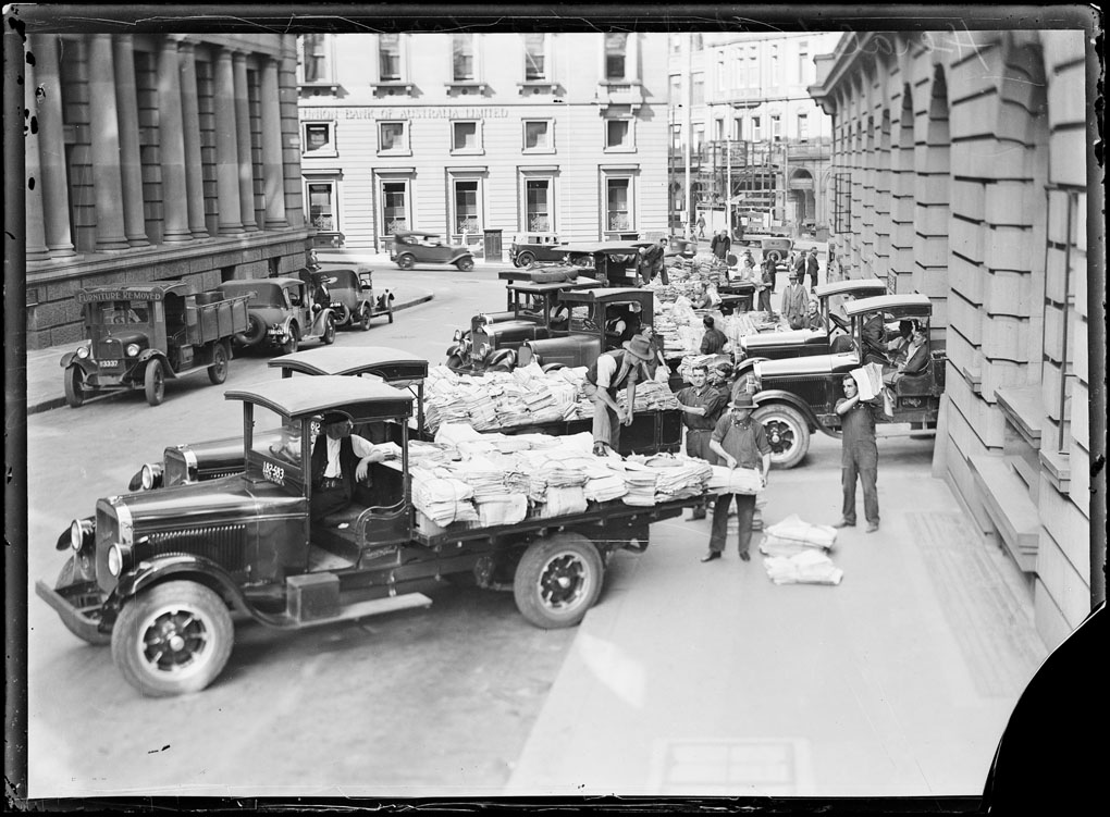 Loading papers into trucks on O'Connell Street, Sydney, ca. 1930 [picture]. [nla.pic-vn6334108]